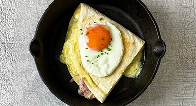 Folded Tortilla in a pan with egg on top