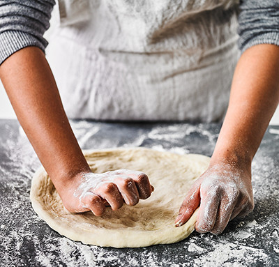 Image of pizza dough shaping to a crust