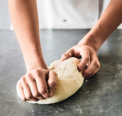Image of pizza dough being kneaded